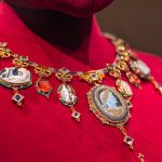 The necklace in the set features gold, enamel, paste diamonds, carnelian, onyx and garnet.