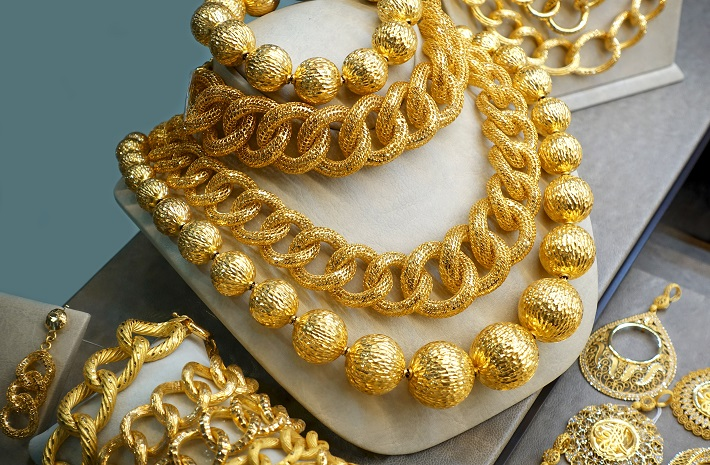 Various gold necklaces, chains and bracelets on the jewelery display.
